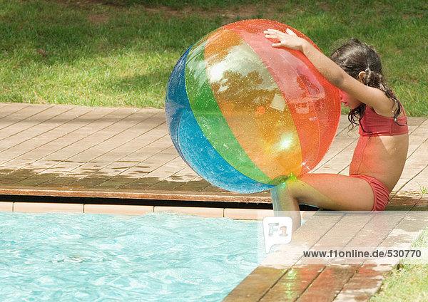 Kleines Mädchen sitzt am Rande des Swimmingpools und hält einen Strandball.