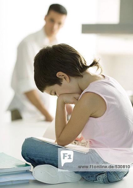 Kind sitzt auf der Theke und macht Hausaufgaben  während Vater kocht.