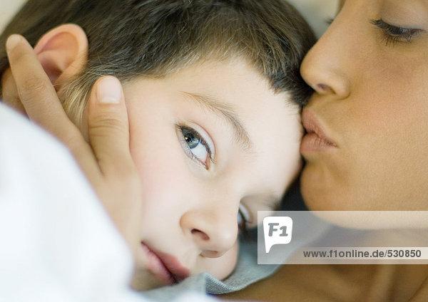 Woman kissing child