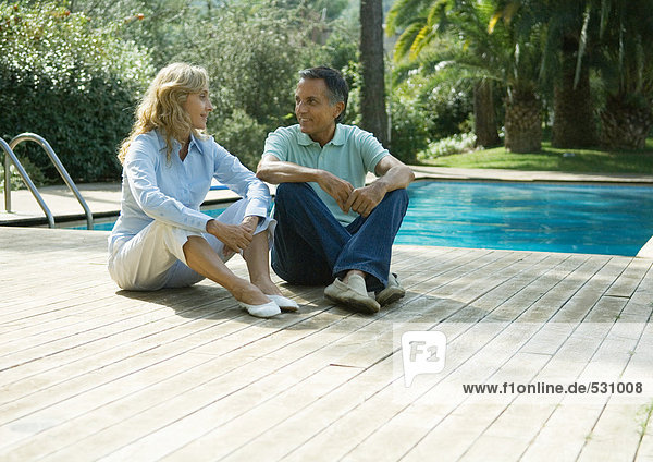 Mature couple sitting on deck by swimming pool