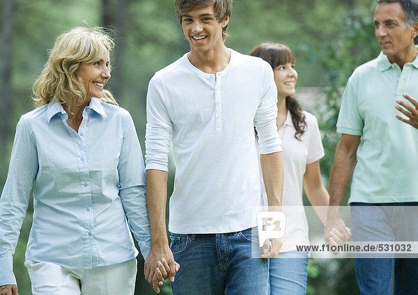 Reife Paare  die mit Teenie-Enkeln Händchen halten.