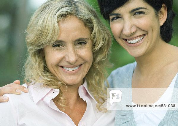 Reife Frau und erwachsene Tochter  lächelnd vor der Kamera