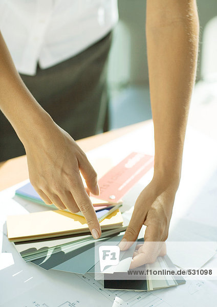 Woman pointing to color swatch  close-up of arms