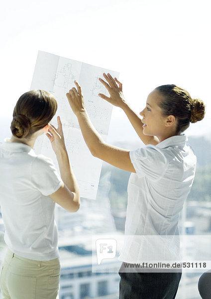 Zwei professionelle Frauen  die sich Blaupausen ansehen und sich unterhalten.