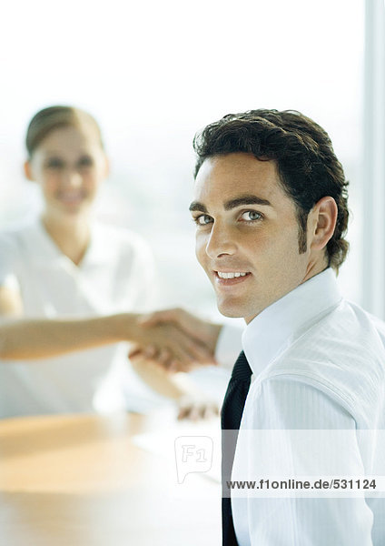 Man and woman shaking hands across table  man smiling over shoulder at camera