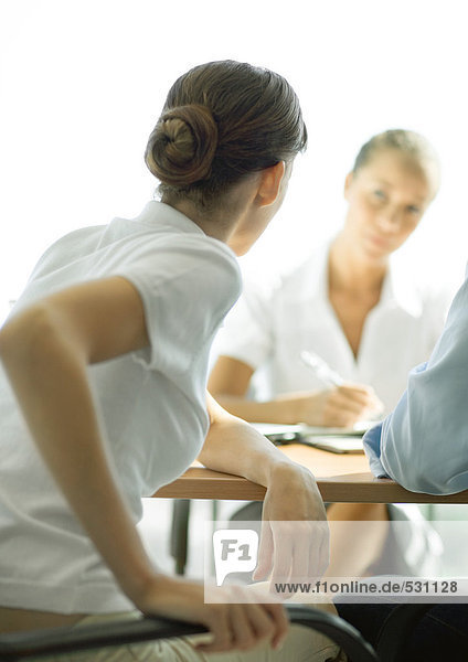 Professional woman sitting at table across from second woman  rear view