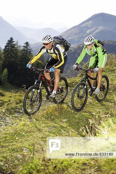Österreich  Tirol  junges Paar beim Radfahren am Berg
