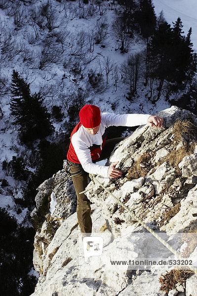 junge Frau  die auf den Felsen klettert.