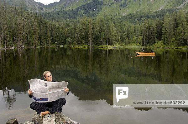 Geschäftsfrau liest Zeitung am See