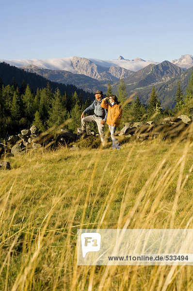 Paar in den Bergen  auf der Wiese stehend