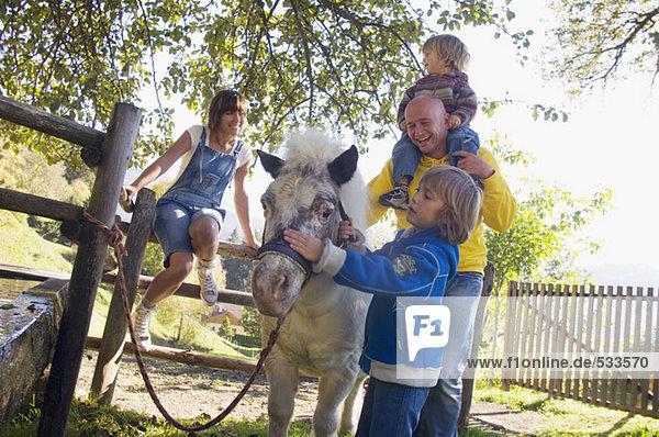 Familie mit Pony am Brunnen