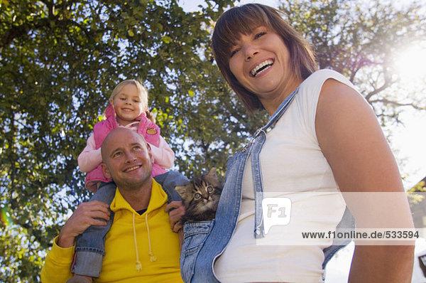 Vater trägt Mädchen auf der Schulter  Mutter hält Kätzchen  niedriger Blickwinkel