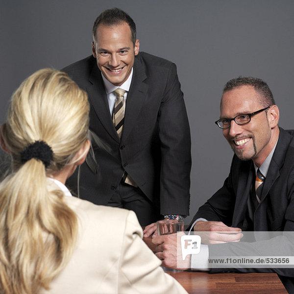 Geschäftsleute  die sich am Konferenztisch treffen  lächelnd