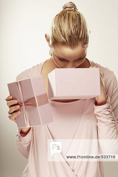 Junge Frau schaut in die Geschenkbox