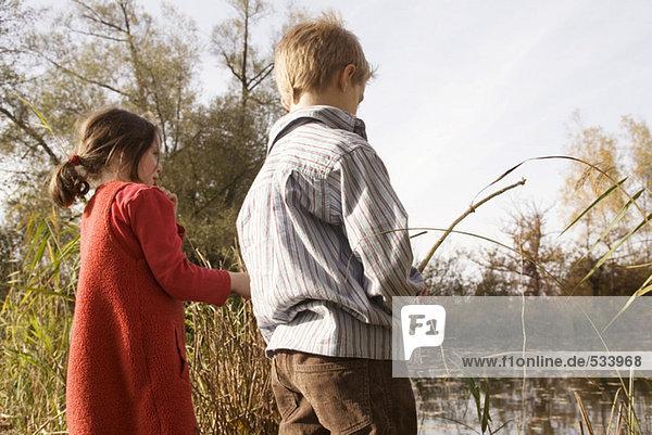 Junge (10-12) und Mädchen (7-9) beim Angeln,  Rückansicht, Junge (10-12) und Mädchen (7-9) beim Angeln,  Rückansicht