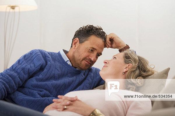 Erwachsenes Paar auf dem Sofa liegend  von Angesicht zu Angesicht  lächelnd