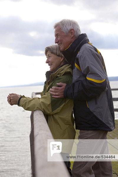 Seniorenpaar am Steg stehend  Seitenansicht