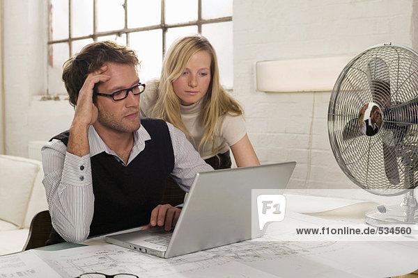 Junger Mann und junge Frau bei der Arbeit am Laptop