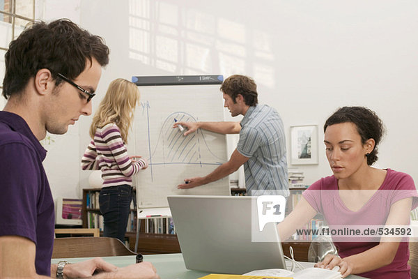 Junge Frau arbeitet am Laptop  Mann erklärt der Frau im Hintergrund den Graphen