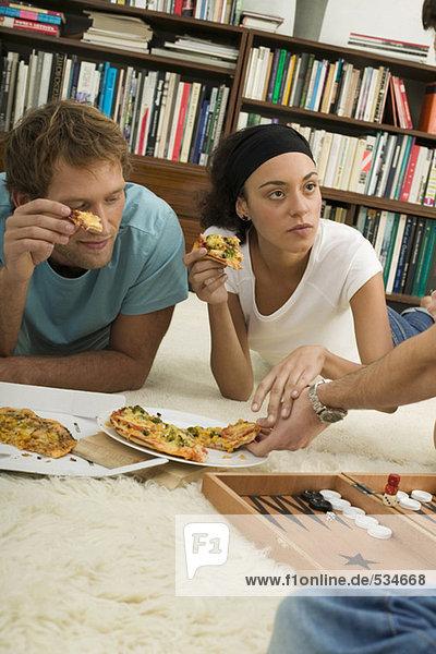 Drei junge Leute liegen auf dem Boden und essen Pizza.