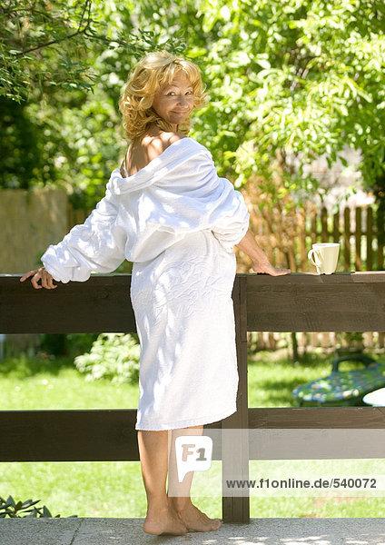 ältere Frau in Bademantel  stehend im Freien mit Robe Herunterfallen Schultern