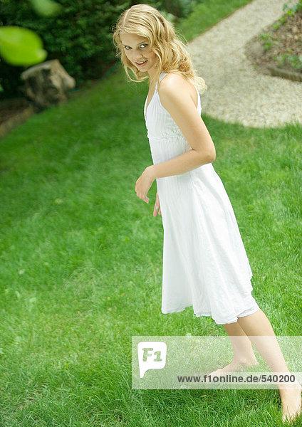 Junge Frau mit weißes Kleid  ständigen barfuß auf Gras