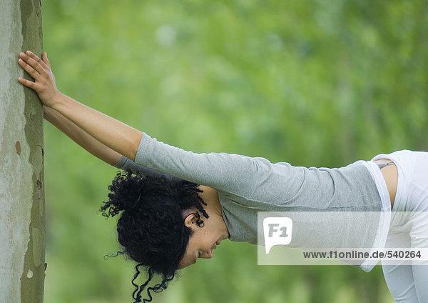 Junge Frau gegen Baum Dehnung