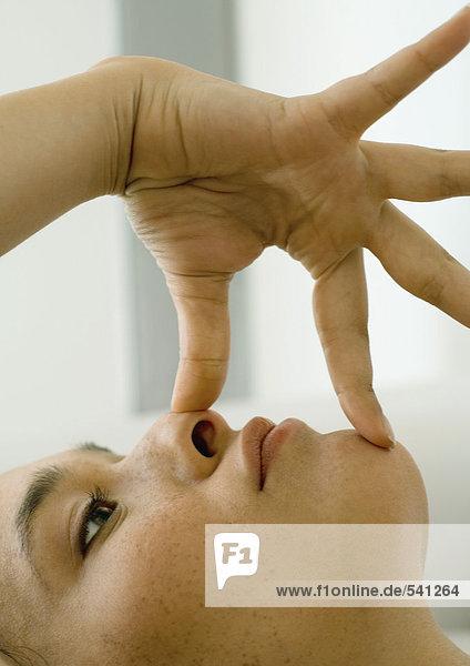 Frau mit Fingern auf Chin und Nase
