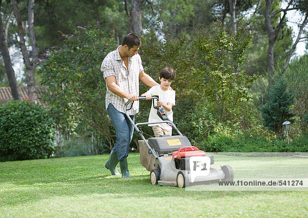 Vater und Sohn mähen Rasen