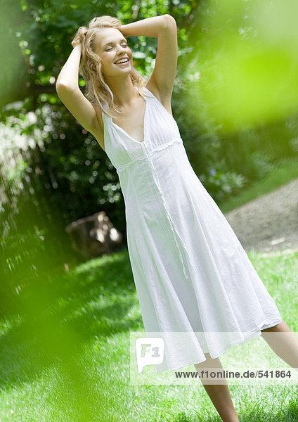 Junge Frau im Hof  Sommerkleid  tragen die Hände in Haar