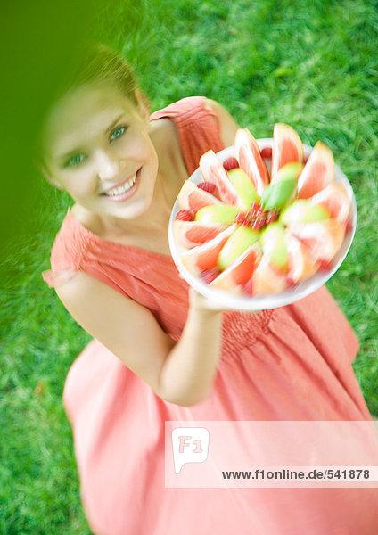Frau halten Sie die up Teller mit Obst Scheiben