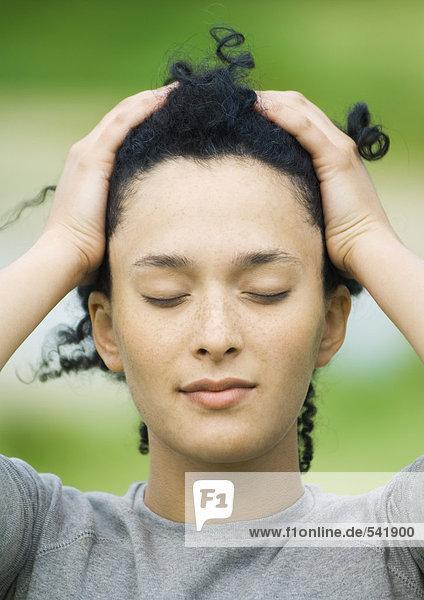 Junge Frau treibend Haar zurück  Augen geschlossen  portrait