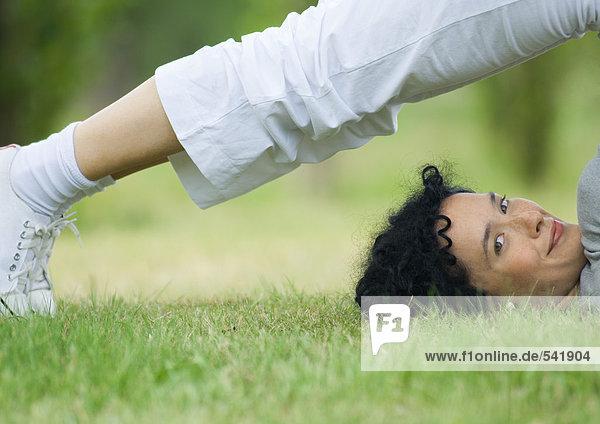 Young Frau macht Pflug-Pose im Freien  Lächeln in die Kamera