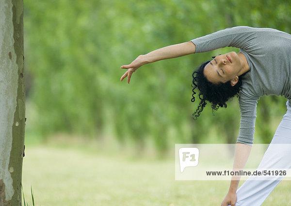 Young Frau macht Seite Stretch Außenaufnahme