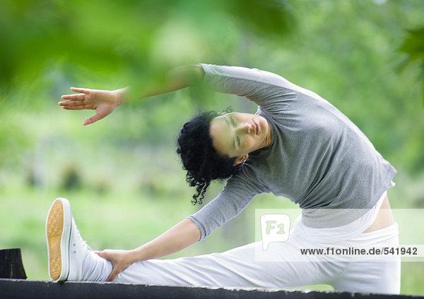 Young Frau macht Seite Stretch auf hölzernen Zaun