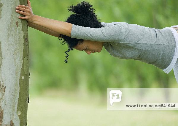 Junge Frau gegen Baumstamm Dehnung
