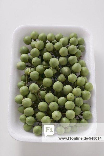 Viele grüne Miniauberginen in weisser Schale