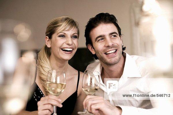 Lachendes Junges Paar mit Weissweinglläsern in der Hand