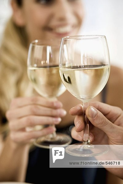 Young clinking white wine glass