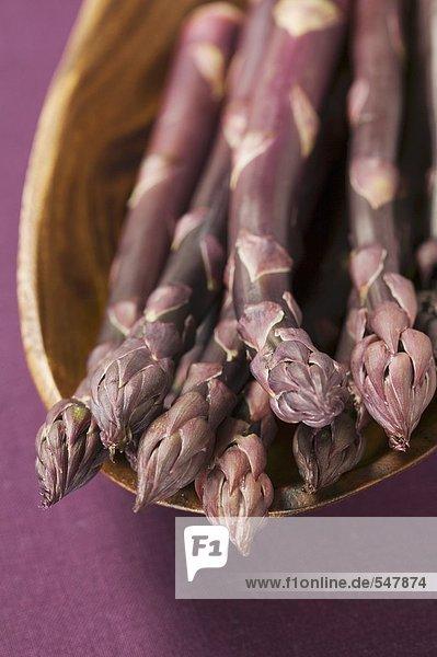 Violetter Spargel in Holzschale
