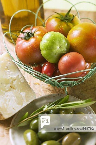 Verschiedene Tomaten im Drahtkorb  Oliven  Käse