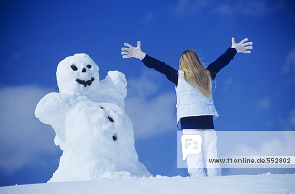 rear view of woman in front of snowman