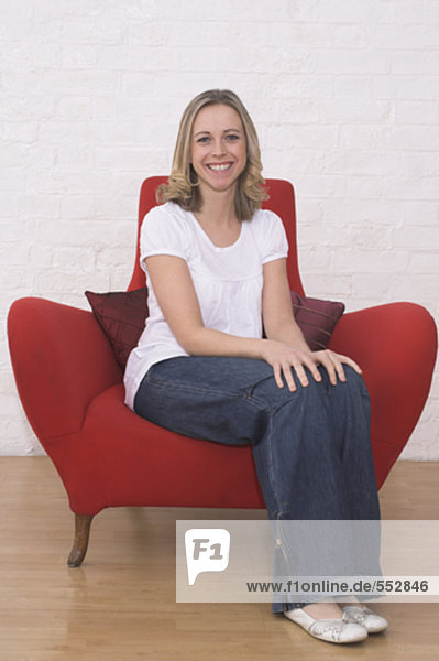 portrait of smiling young woman sitting in red armchair