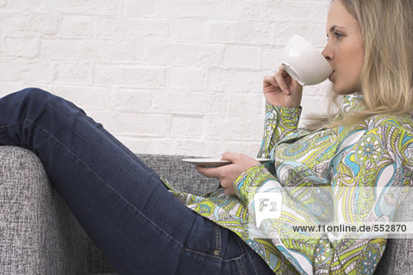 side view of young woman relaxing on armchair drinking cup of tea