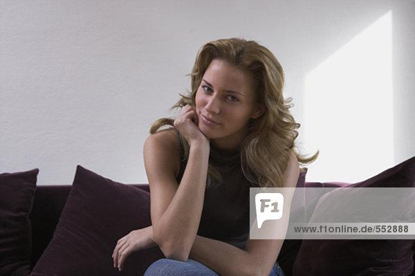 Portrait einer jungen Frau sitzen auf Sofa Blick in die Kamera