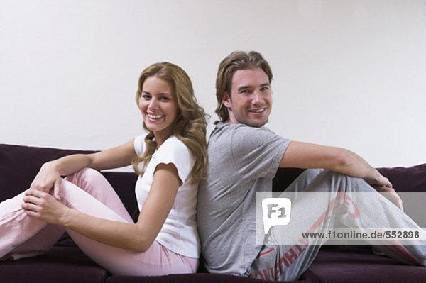 glückliches paar sitzen wieder auf sofa