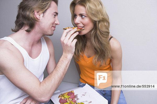 Interior  zu Hause  Frau  Mann  jung  Pizza  füttern  Stück