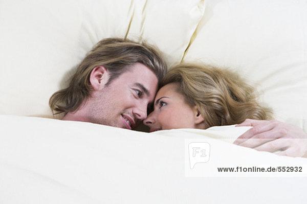 Kopfschuss von paar liegend im Bett glücklich schauen einander