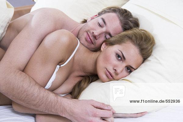 junges paar liegend im Bett suchen verärgert weiblich zusammen