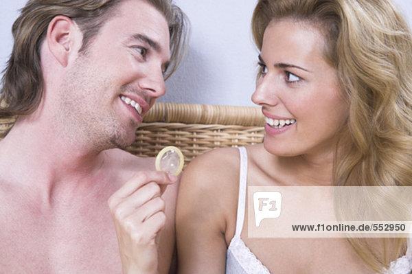 junges Paar im Bett Frau hält Kondom sitzen